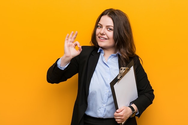 Young curvy plus size business woman holding a clipboard cheerful and confident showing ok gesture.