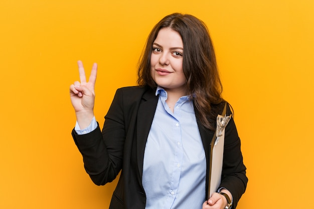 Young curvy plus size business woman holding a clipboard showing number two with fingers.