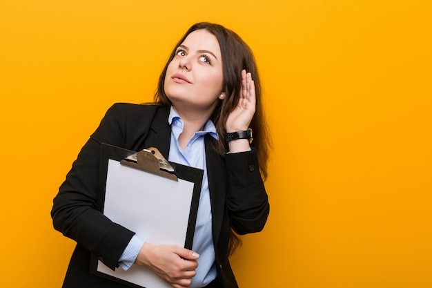 Young curvy plus size business woman holding a clipboard trying to listening a gossip.