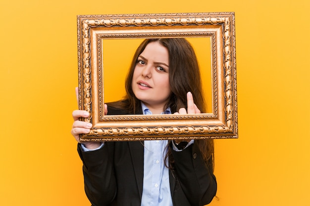 Young curvy plus size business woman holding a frame pointing with finger at you as if inviting come closer.