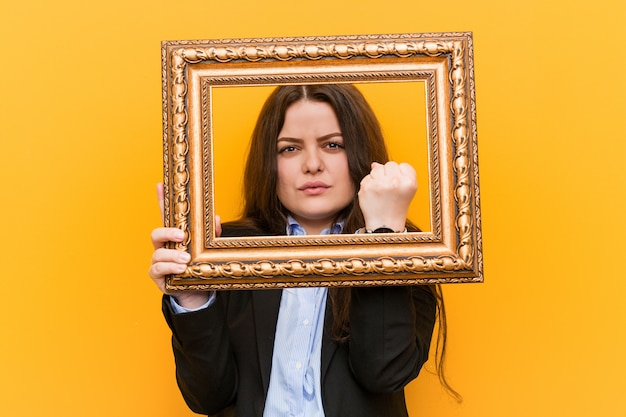 Young curvy plus size business woman holding a frame showing in aggressive facial expression.