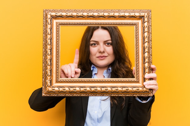 Young curvy plus size business woman holding a frame showing number one with finger.