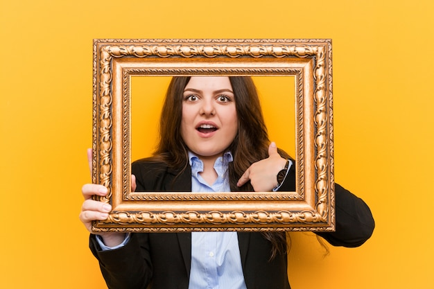 Young curvy plus size business woman holding a frame surprised pointing at himself, smiling broadly.