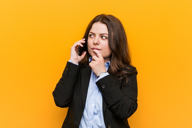 Young curvy plus size business woman holding a phone looking sideways with doubtful and skeptical expression.