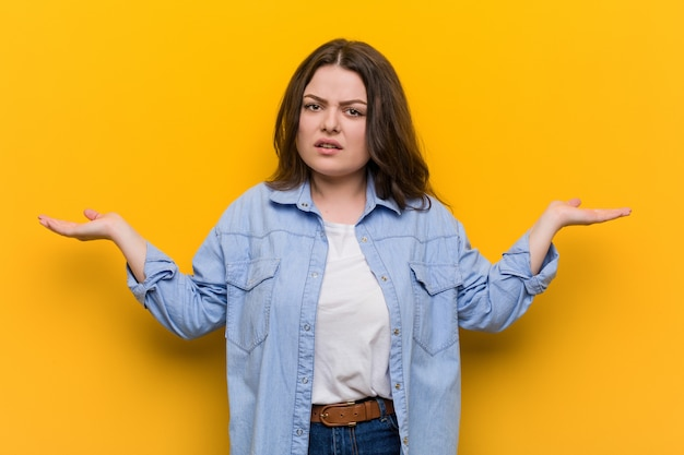Young curvy plus size woman confused and doubtful raising him hands to hold a copy space.