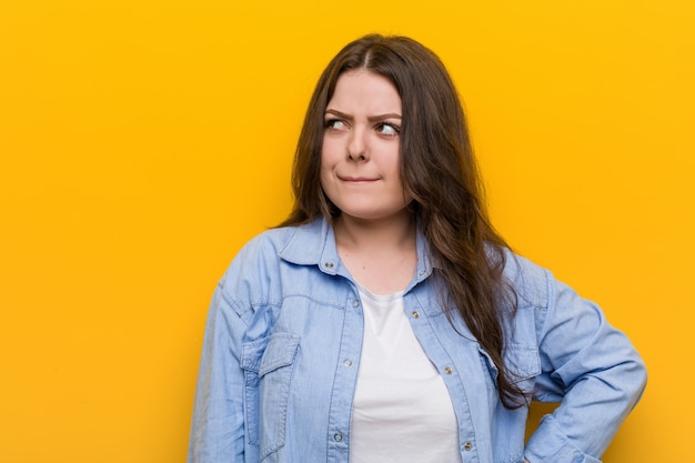 Young curvy plus size woman confused, feels doubtful and unsure.