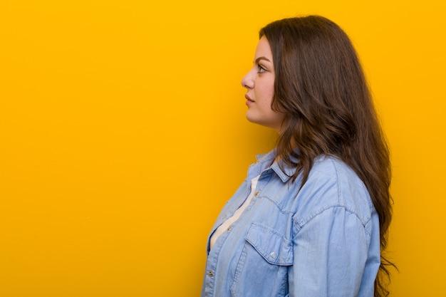 Young curvy plus size woman gazing left, sideways pose.