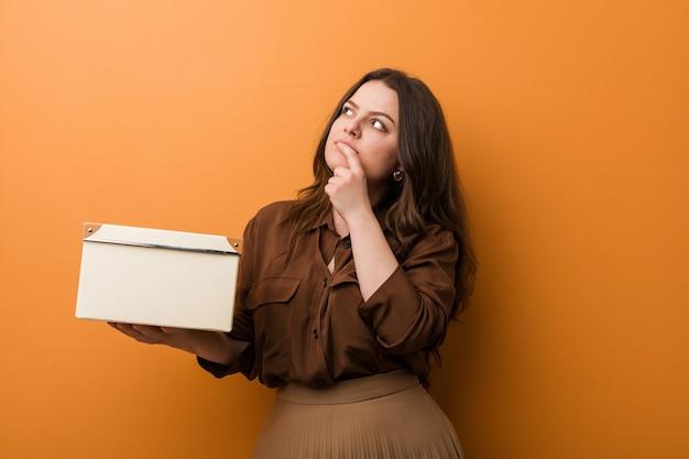 疑わしいと懐疑的な表情で横向きの箱を持っている若い曲線美のプラスサイズの女性。