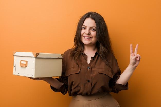 指で2番目を示すボックスを保持している若い曲線美プラスサイズの女性。