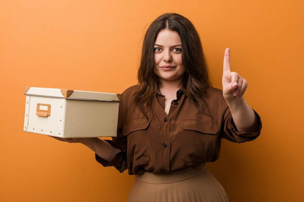 Young curvy plus size woman holding a box showing number one with finger.