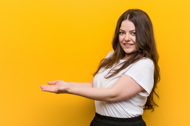 Young curvy plus size woman holding a copy space on a palm.