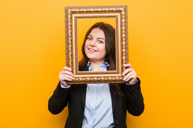 Young curvy plus size woman holding a frame happy, smiling and cheerful.