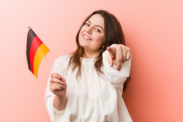 Young curvy plus size woman holding a germany flag cheerful smiles pointing to front.