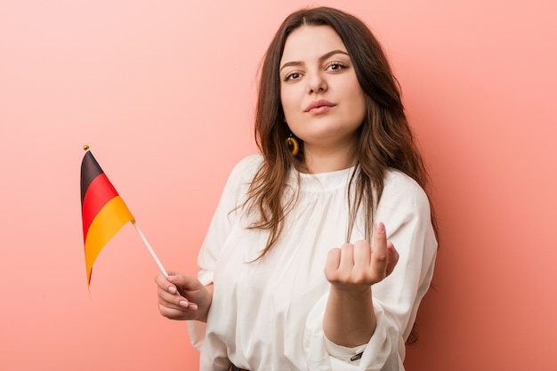 Young curvy plus size woman holding a germany flag pointing with finger at you as if inviting come closer.