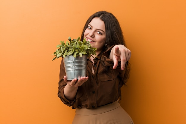 Young curvy plus size woman holding a plant cheerful smiles pointing to front.