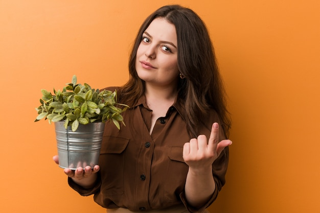 Young curvy plus size woman holding a plant pointing with finger at you as if inviting come closer.