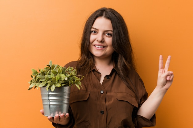 Young curvy plus size woman holding a plant showing number two with fingers.
