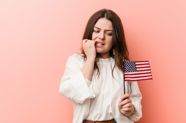 Young curvy plus size woman holding a united states flag biting fingernails, nervous and very anxious.