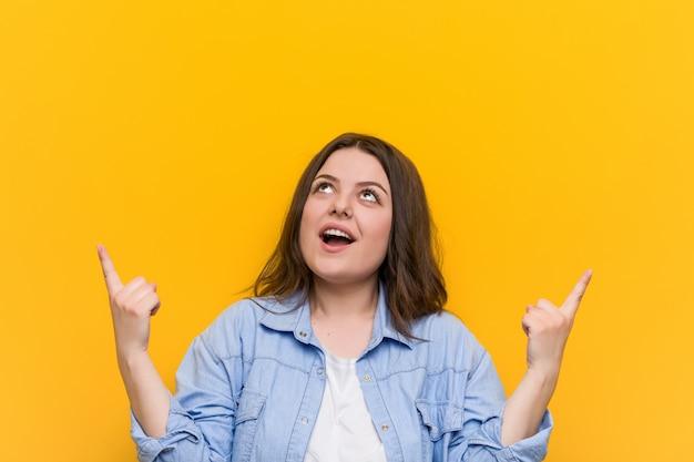 若い曲線美のプラスのサイズの女性は、両指で空白を示しています。