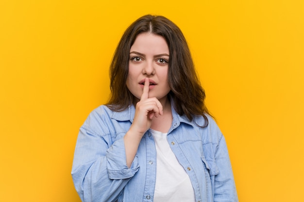 Young curvy plus size woman keeping a secret or asking for silence.
