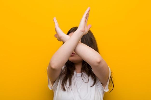 若い曲がりくねったプラスサイズの女性が2本の腕を組んでいる、否定の概念。