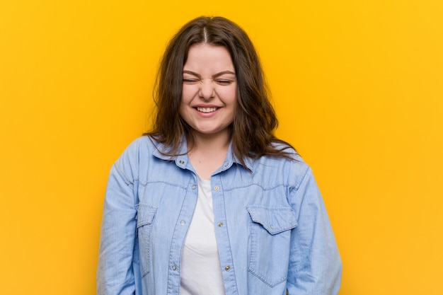 Young curvy plus size woman laughs and closes eyes, feels relaxed and happy.