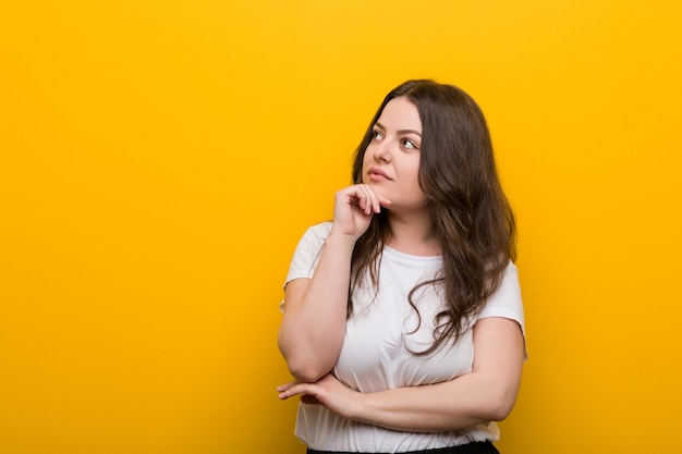 Young curvy plus size woman looking sideways with doubtful and skeptical expression.