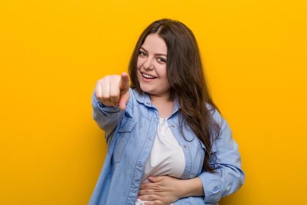 若い曲線美のプラスサイズの女性は親指の指を離れて、笑ってのんきなポイント。
