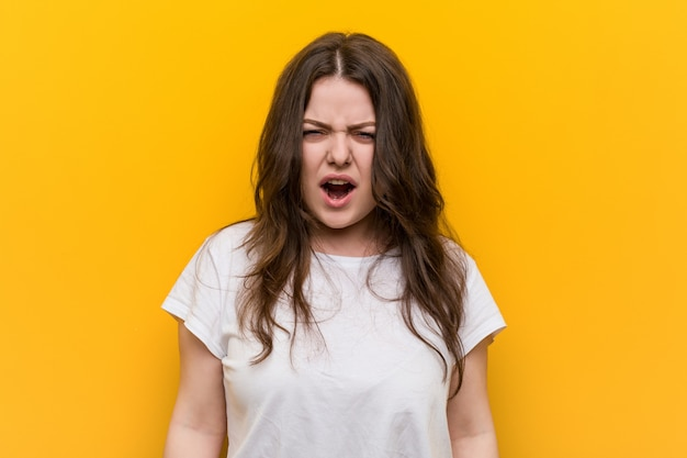 Young curvy plus size woman screaming very angry and aggressive.