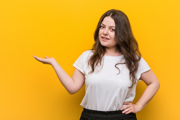 Young curvy plus size woman showing a copy space on a palm and holding another hand on waist.