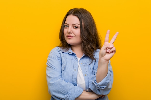 Young curvy plus size woman showing number two with fingers.