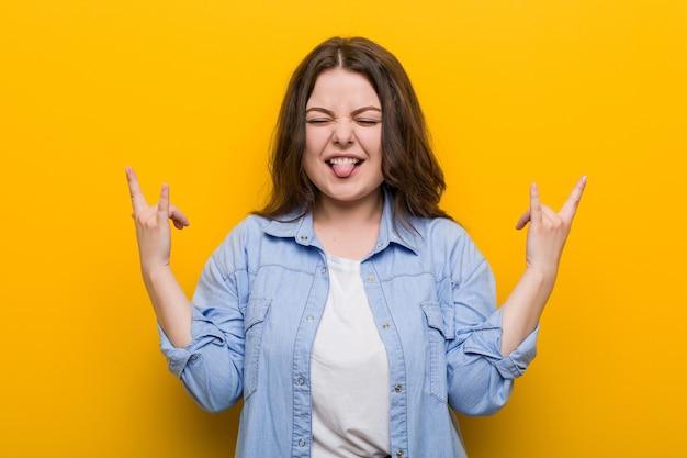 指でロックジェスチャーを示す若い曲線美プラスサイズの女性
