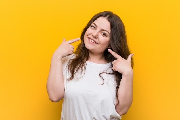 Young curvy plus size woman smiles, pointing fingers at mouth.