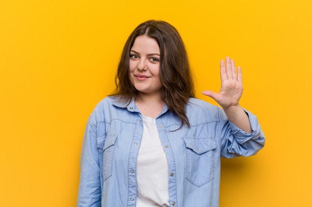Young curvy plus size woman smiling cheerful showing number five with fingers.