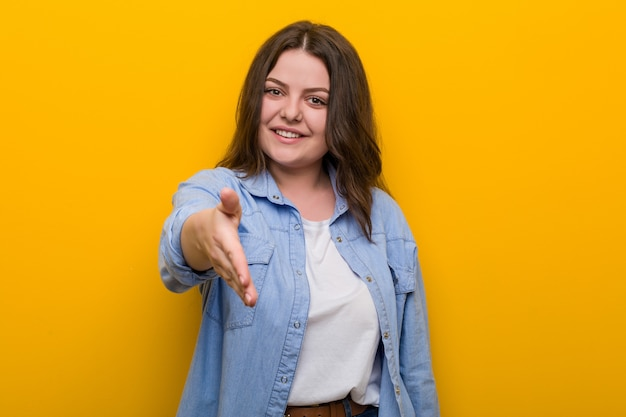 Young curvy plus size woman stretching hand in greeting gesture.