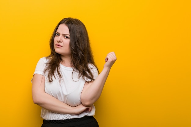 Young curvy plus size woman touching back of head, thinking and making a choice.