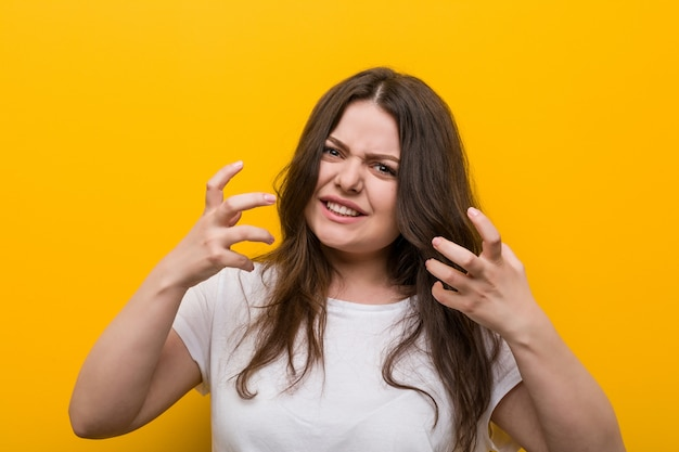 Young curvy plus size woman upset screaming with tense hands.