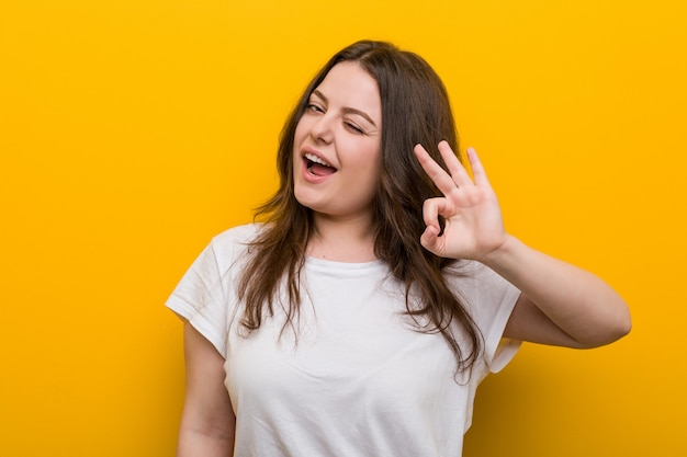 Young curvy plus size woman winks an eye and holds an okay gesture with hand.