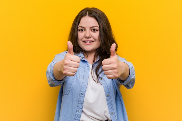 Young curvy plus size woman with thumbs ups, cheers about something, support and respect .