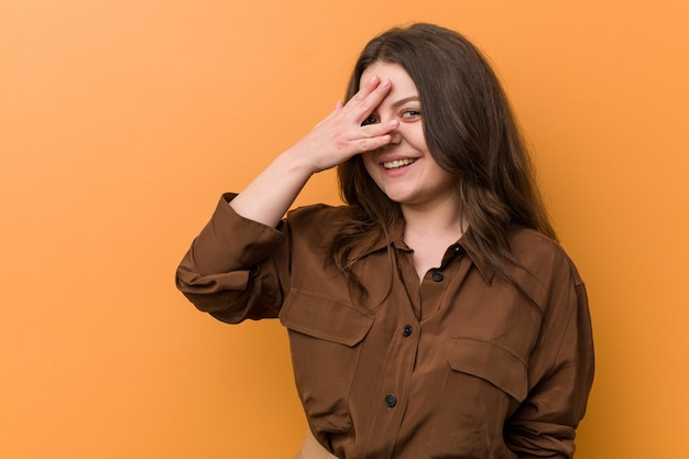 Young curvy russian woman blink at the camera through fingers, embarrassed covering face.