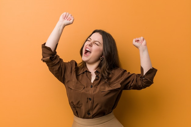 Young curvy russian woman celebrating a special day, jumps and raising arms with energy.