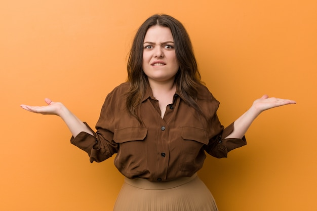 Young curvy russian woman confused and doubtful raising him hands to hold a copy space.