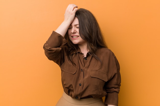 Young curvy russian woman forgetting something, slapping forehead with palm and closing eyes.