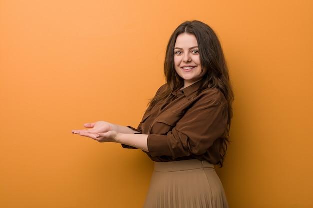 手のひらにコピースペースを保持している若い曲線美のロシアの女性。