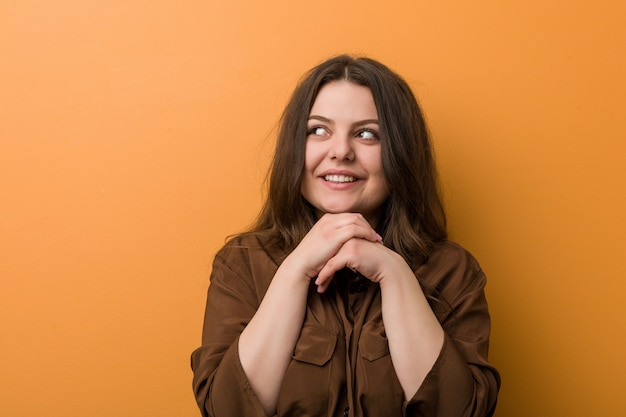 Young curvy russian woman keeps hands under chin, is looking happily aside.