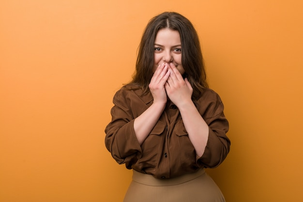 Young curvy russian woman laughing about something, covering mouth with hands.