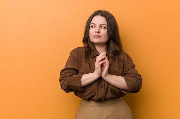 Young curvy russian woman making up plan in mind, setting up an idea.