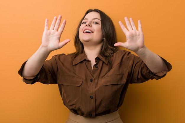 手で10番を示す若い曲線美のロシアの女性。