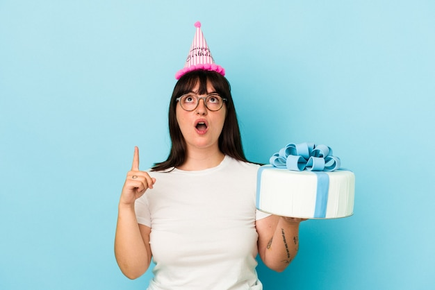 Young curvy woman celebrating her birthday isolated on blue background pointing upside with opened mouth.