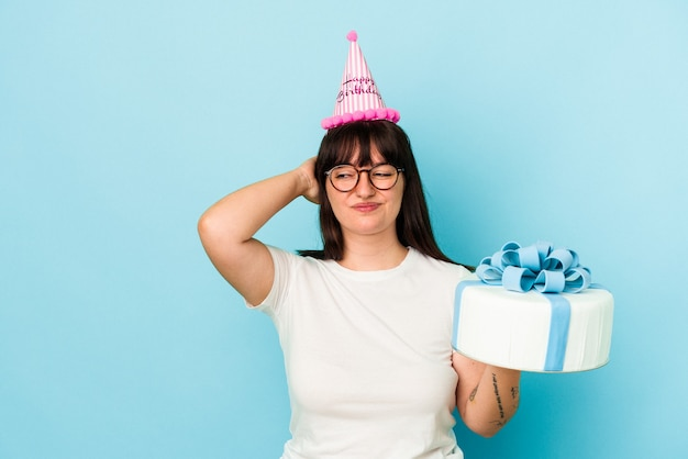 Young curvy woman celebrating her birthday isolated on blue background touching back of head, thinking and making a choice.